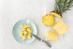Cut Pineapple on Marble Chopping Board and Plate. Arrangement of a cut pineapple on a white marble chopping board and a blue plate with knife on a white marbled Royalty Free Stock Photography