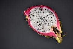 Cut pitahaya on black background close up, dragon fruit stock photo