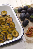 Cut plums in an enamel bowl Stock Photo