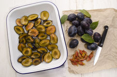 Cut plums in an enamel bowl Stock Image