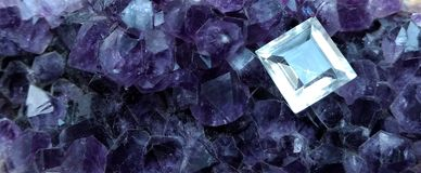 Cut and polished topaz on a bed of amethyst crystals. Single colourless cut topaz from Sri Lanka sits on top a bed of natural purple amethyst crystals stock photo
