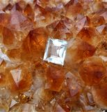 Cut and polished topaz on a bed of citrine crystals. Single colourless cut topaz from Sri Lanka sits on top a bed of natural purple citrine quartz crystals stock images