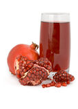 The cut pomegranate and garnet juice in a glass. Stock Photography