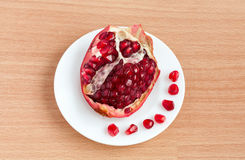 The cut pomegranate and grains on a plate Royalty Free Stock Images