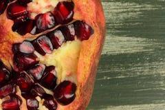 Cut pomegranate helpful. On a wooden board cut is useful grenades stock photo