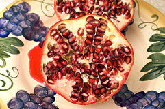 Cut pomegranate on plate. Showing the red juicy seeds in rows Stock Image