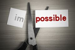 Cut possible from impossible. A scissor is cuting possible from impossible on the desk Royalty Free Stock Image