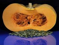Cut pumpkin. Longitudinal section of orange pumpkin and peeled seeds on a blue table Stock Photos