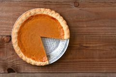 Cut Pumpkin Pie on Wood Table Stock Images