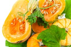 Cut pumpkin with pumpkin seeds and green leaves. Isolated on white background Royalty Free Stock Photo