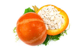 Cut pumpkin with pumpkin seeds and green leaves Stock Photography