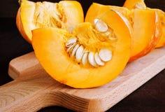 Cut pumpkin on a wooden board. Royalty Free Stock Image