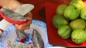 Cut and putting fresh exotic fruits on the plate stock video footage