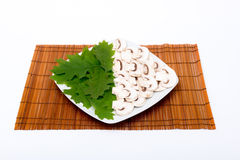 Cut raw mushrooms and leaves Stock Photos
