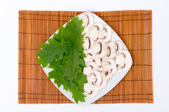Cut raw mushrooms and leaves Stock Photography