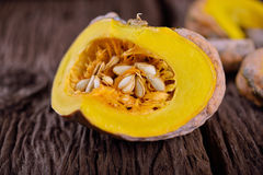 Cut raw pumpkin with seed on wooden background Stock Image