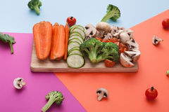 Cut raw vegetables on wooden board, healthy food. Wooden board with cut organic raw vegetables on bright geometric background. Healthy food, copy space Royalty Free Stock Photos
