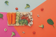 Cut raw vegetables on wooden board, healthy food. Wooden board with cut organic raw vegetables on bright geometric background. Healthy food, copy space Stock Photo