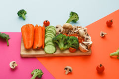Cut raw vegetables on wooden board, healthy food. Wooden board with cut organic raw vegetables on bright geometric background. Healthy food, copy space Stock Photography