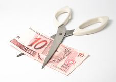 Cut the real. Scissors cutting ten brazilian reais (real) banknote Royalty Free Stock Image