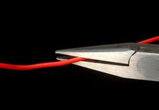 Cut the red cable!!. Plier cutting red cable on black background Royalty Free Stock Photo