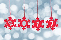 2017 cut in red fabric christmas ornaments hanging on bokeh background, new year decoration Stock Photos