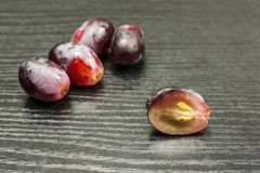Cut red grape on a wooden table and whole fruit in the backgroun. Cut red grape on a wooden table and a few whole fruits in the background Royalty Free Stock Photography