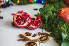 Cut red pomegranate, cinnamon, dried lemons lie on white wooden table on a background of green Christmas garland and lights Royalty Free Stock Images