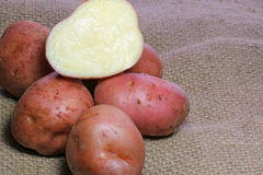 Cut red potatoes on burlap. Stock Images