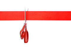Cut red ribbon. Scissors cutting red ribbon or tape against white background Royalty Free Stock Images