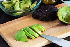 Cut ripe avocado Haas on cutting board. Dark wooden background. stock photo