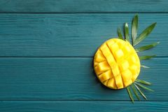 Cut ripe mango and palm leaf on wooden background stock photography