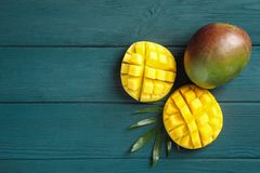 Cut ripe mangoes and palm leaf on wooden background royalty free stock photo
