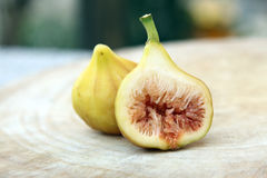 Cut through of ripe yellow fig fruit on blur background. royalty free stock photos