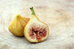 Cut through of ripe yellow fig fruit on wooden background. royalty free stock photography