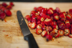 Cut rosehips on chopping board with knife Royalty Free Stock Images