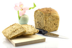 Cut rye bread loaf and a flower in a vase, isolate. Fresh sliced whole grain bread on wooden board with knife, flower in the background Royalty Free Stock Photo