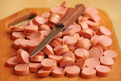 Cut sausage with a knife. Cut sausage on a chopping board with a knife Royalty Free Stock Photos