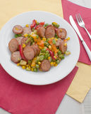 Cut sausages and vegetables plate top view Stock Photos
