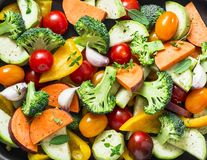 Cut seasonal raw vegetables - sweet potatoes, broccoli, bell peppers, zucchini, tomatoes, onions, garlic with spices and herbs. In stock images