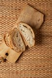 Cut bread showing air texture of flour on wood block with weave background and copy space. Royalty Free Stock Photography