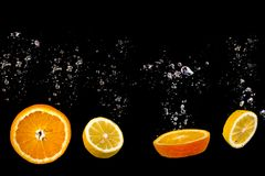 Cut Orange and lemon floats on water with bubbles, fruits is on a black background royalty free stock image