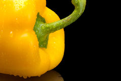 Cut shot of yellow bell pepper isolated on black with water drop Royalty Free Stock Photos