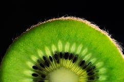 Cut slice of kiwi fruit close-up on black background horizontal. Stock Photos