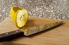 A cut slice of lemon on a board with a knife stock photos
