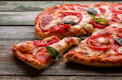 Cut of slice pizza with cheese on green wood table Royalty Free Stock Photo