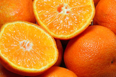 Cut or sliced oranges as a background. A closeup of oranges including a juicy cut or sliced fruit Royalty Free Stock Images