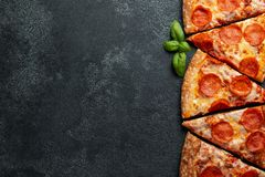 Cut into slices delicious fresh pizza with sausage pepperoni and cheese on a dark background. Top view with copy space. For text. Pizza on the black concrete stock images
