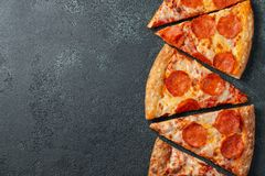 Cut into slices delicious fresh pizza with sausage pepperoni and cheese on a dark background. Top view with copy space for text. Pizza on the black concrete stock photo