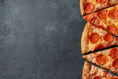 Cut into slices delicious fresh pizza with sausage pepperoni and cheese on a dark background. Top view with copy space for text. Pizza on the black concrete stock photos
